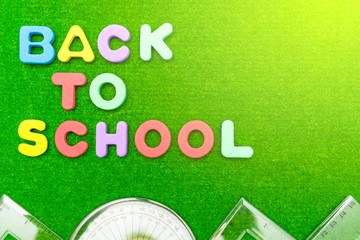 back to school lettering with school supplies on green grass with sunlight background