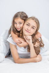 portrait of embracing daughter and mother on bed