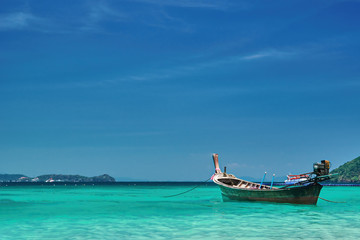 Fishing wooden boat at noon. Tropical sea in the background. Thailand. Panorama landscape.