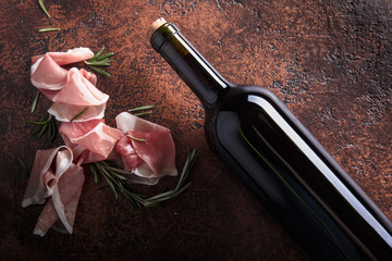 Prosciutto with rosemary and bottle of red wine.