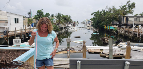 Terri Metter stands in front of what's left of destroyed trailers, that fill a canal near a trailer park in Marathon