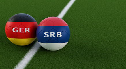 Germany vs. Serbia Soccer Match - Soccer balls in Germanys and Serbias national colors on a soccer field. Copy space on the right side - 3D Rendering