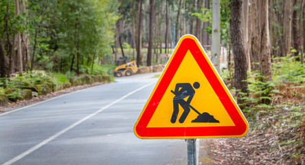 temporary road sign indicating work on a small road in the forest