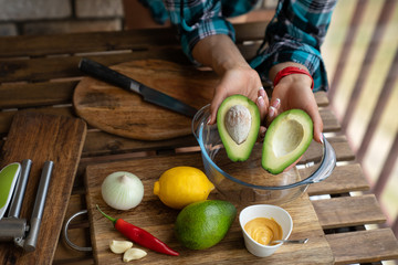 young woman cuts avocado on cutting board on table close up