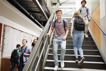 High School Students Walking Down Stairs In Busy College Building