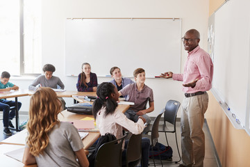 Male High School Tutor Standing At Whiteboard Teaching Class