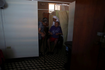 A nun helps an elderly man in a wheelchair next to another resident of the San Rafael nursing home in Arecibo