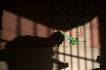 A nun casts her shadow on a painting with the imprints of the hands of residents of the San Rafael nursing home in Arecibo
