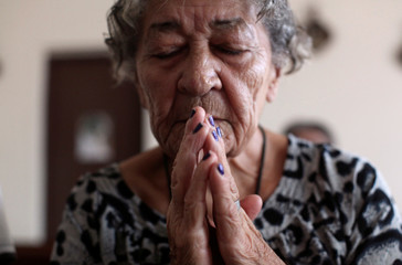 An elderly woman prays at a chapel of the San Rafael nursing home in Arecibo