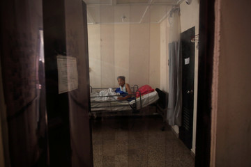 An elderly woman sits in her bed at the San Rafael nursing home in Arecibo