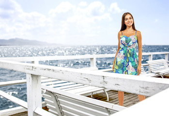 slim young woman on white wooden pier and sea landscape