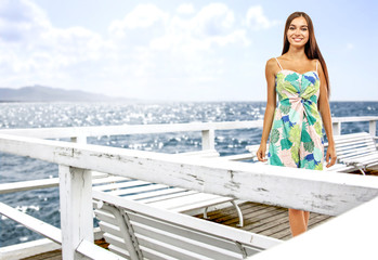 Slim young woman on white pier and sea lanscape