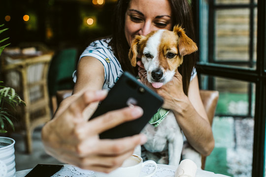 Young beautiful woman having great time with her little sweet dog in a restaurant after their meal, taking many pictures. Lifestyle and friendship concept.