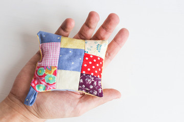patchwork, quilting, sewing, tailoring and fashion concept - close-up on beautiful colorful stitched pincushion in human hand, macro on pillow with white background, flat lay, top view.
