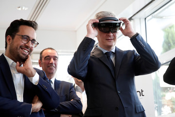 Mounir Mahjoubi, French Junior Minister in Charge of Digital Sector, reacts as French Finance Minister Bruno Le Maire wears a virtual reality headset during a visit of the new Qwant headquarters in Paris