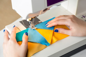 equipment, clothing, hobby concept. there is a close up of delicate arms of dressmaker who is working at the table with help of sewing machine, she is stitching few pieces of fabric