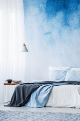 Bed with grey blanket against blue ombre wall in bedroom interior with lamp above table