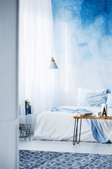 Patterned rug in modern, pastel blue bedroom interior with bed against ombre wall
