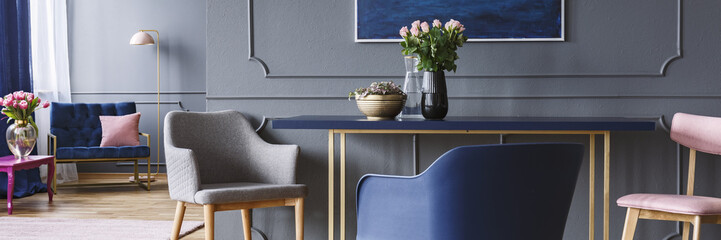 Chairs standing by the blue and gold dining table with pink roses in vase in dark grey open space living room interior