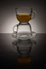 Two glass cup with tea and saucer on a black and white background