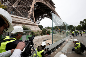 Members of the media make images of the new glass security fence which is under construction around the Eiffel Tower in Paris