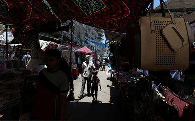 Palestinians shop in a market ahead of the upcoming Eid al-Fitr holiday marking the end of the Muslim holy month of Ramadan, in Rafah in the southern Gaza Strip