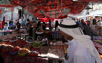 Vendor sells sweets as Palestinians shop in a market ahead of the upcoming Eid al-Fitr holiday marking the end of the Muslim holy month of Ramadan, in Rafah in the southern Gaza Strip