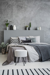 Striped carpet and stool in grey bedroom interior with sheets on bed with headboard. Real photo