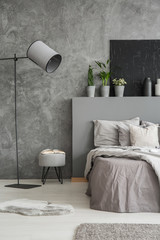 Lamp and stool next to bed with pillows and bedhead in grey bedroom interior with poster. Real photo