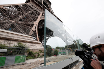 A member of the media makes images of the new glass security fence which is under construction around the Eiffel Tower in Paris