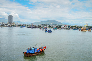 fishing schooners in the parking lot, in the riverbed of the Kai River, on the background buildings, mountains, and the sky covered with clouds, Nha Trang, Vietnam