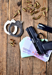 View from above of 9mm pistol gun - handgun, handcuffs, special police hollow-point expanding bullets, euro banknotes and magazine on old wooden table