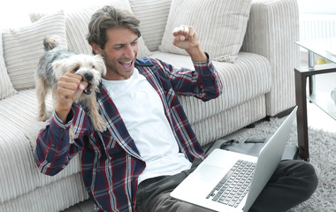 happy guy rejoicing and raising his hands sitting near the sofa in the living room.