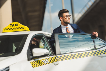 hansome young man in suit and eyeglasses looking away while sitting in taxi cab