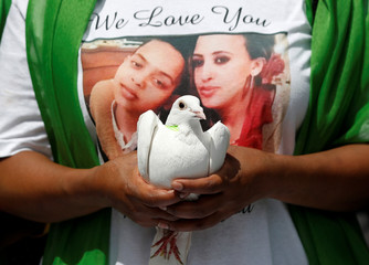 A man holds a dove during commemorations to mark the first anniversary of the Grenfell Tower fire, near the burn out social housing apartment block in west London