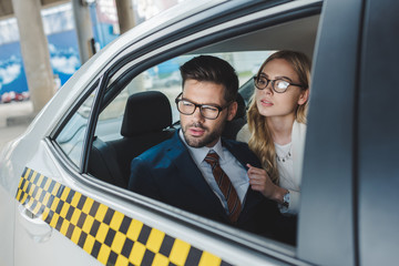 stylish young couple in formal wear and eyeglasses looking away while sitting together in taxi