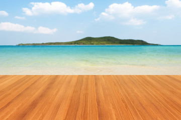 Wooden table or wood floor isolated on beach with mountain and cloudy background. For your product placement or montage with focus to the table top in the foreground. Empty wood orange shelf. shelves