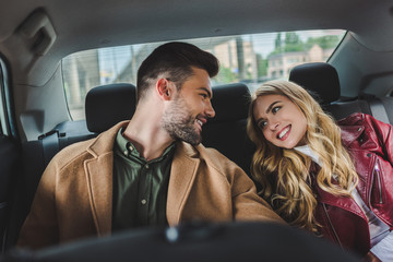 beautiful happy young couple smiling each other while sitting together in car