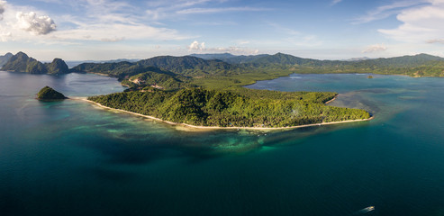 Aerial drone panoramic view of a beautiful tropical beach and reef in the evening (Las Cabanas, Palawan)