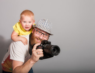 "A photographer with a child in his arms takes an enthusiastic photograph against a gray background in the studio. The concept of ""Children of Photography is not a hindrance"""