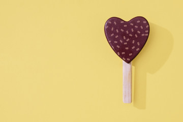 Heart shaped ice cream popsicle on pastel background for summer.  Wooden toy ice lollipops