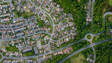 Top down aerial view of an urban area in a small town surrounded by trees and greenery Fotomurales