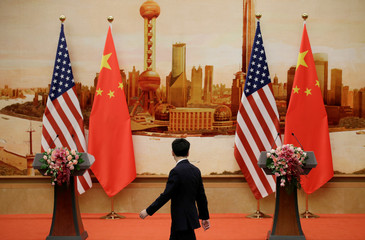 A staff member walks past U.S. and Chinese flags placed for a joint news conference in Beijing