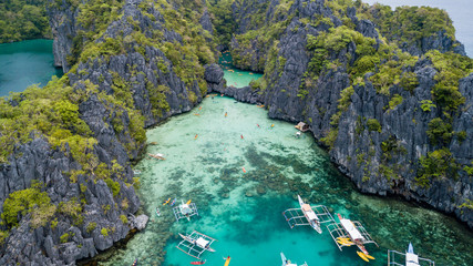 Aerial drone view of wooden boats and kayaks inside a beautiful shallow tropical lagoon surrounded by jagged cliffs (Small and Big Lagoon, El Nido)