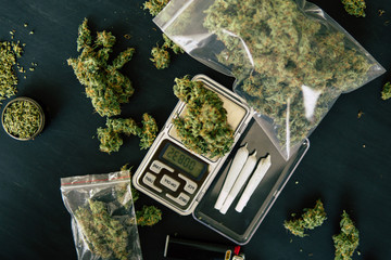 grinder and shredded cannabis joint and a packet of weed and Smartphone on a black wood background top Bud of marijuana flowers on scales,