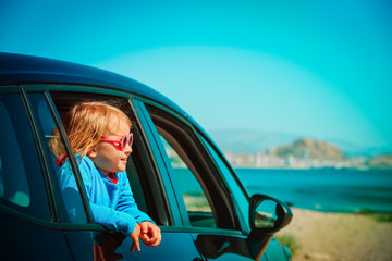 happy little girl enjoy travel by car at beach