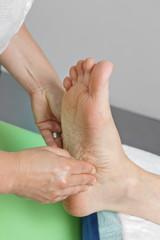 femme pratiquant réflexologie plantaire sur pied homme mature