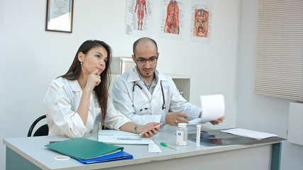 Dreamy female doctor asking her colleague what to answer to a phone message