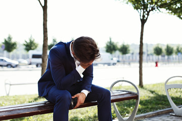 Sad businessman sits on the bank outside the street
