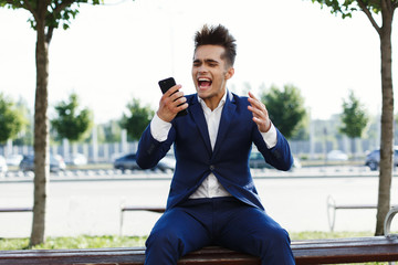 Happy young businessman holds smartphone in his arm and screams sitting on the street
